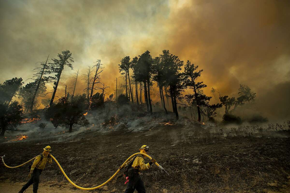 A hillside smolders as firefighters light backfires to slow the spread of the Kincade Fire in unincorporated Sonoma County, Calif., near Geyservillle on Saturday, Oct. 26.