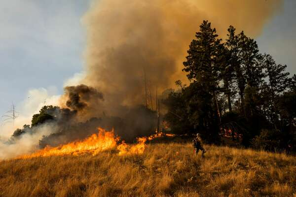 A firefighter sets a back fire along a hillside during firefighting operations to battle the Kincade Fire in Healdsburg, California on October 26, 2019. - US officials on October 26 ordered about 50,000 people to evacuate parts of the San Francisco Bay area in California as hot dry winds are forecast to fan raging wildfires.