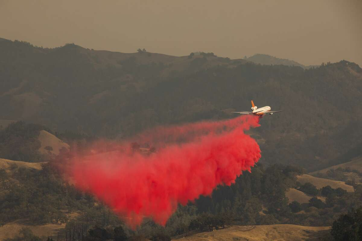An air tanker drops fire retardant in the valley below during the firefighting operations to battle the Kincade Fire in Healdsburg, California on October 26, 2019. - US officials on October 26 ordered about 50,000 people to evacuate parts of the San Francisco Bay area in California as hot dry winds are forecast to fan raging wildfires. (Photo by Philip Pacheco / AFP) / The erroneous source appearing in the metadata of this photo by Philip Pacheco has been modified in AFP systems in the following manner: [AFP] instead of [www.philippachecophoto.com]. Please immediately remove the erroneous mention from all your online services and delete it from your servers. If you have been authorized by AFP to distribute it to third parties, please ensure that the same actions are carried out by them. Failure to promptly comply with these instructions will entail liability on your part for any continued or post notification usage. Therefore we thank you very much for all your attention and prompt action. We are sorry for the inconvenience this notification may cause and remain at your disposal for any further information you may require. (Photo by PHILIP PACHECO/AFP via Getty Images)
