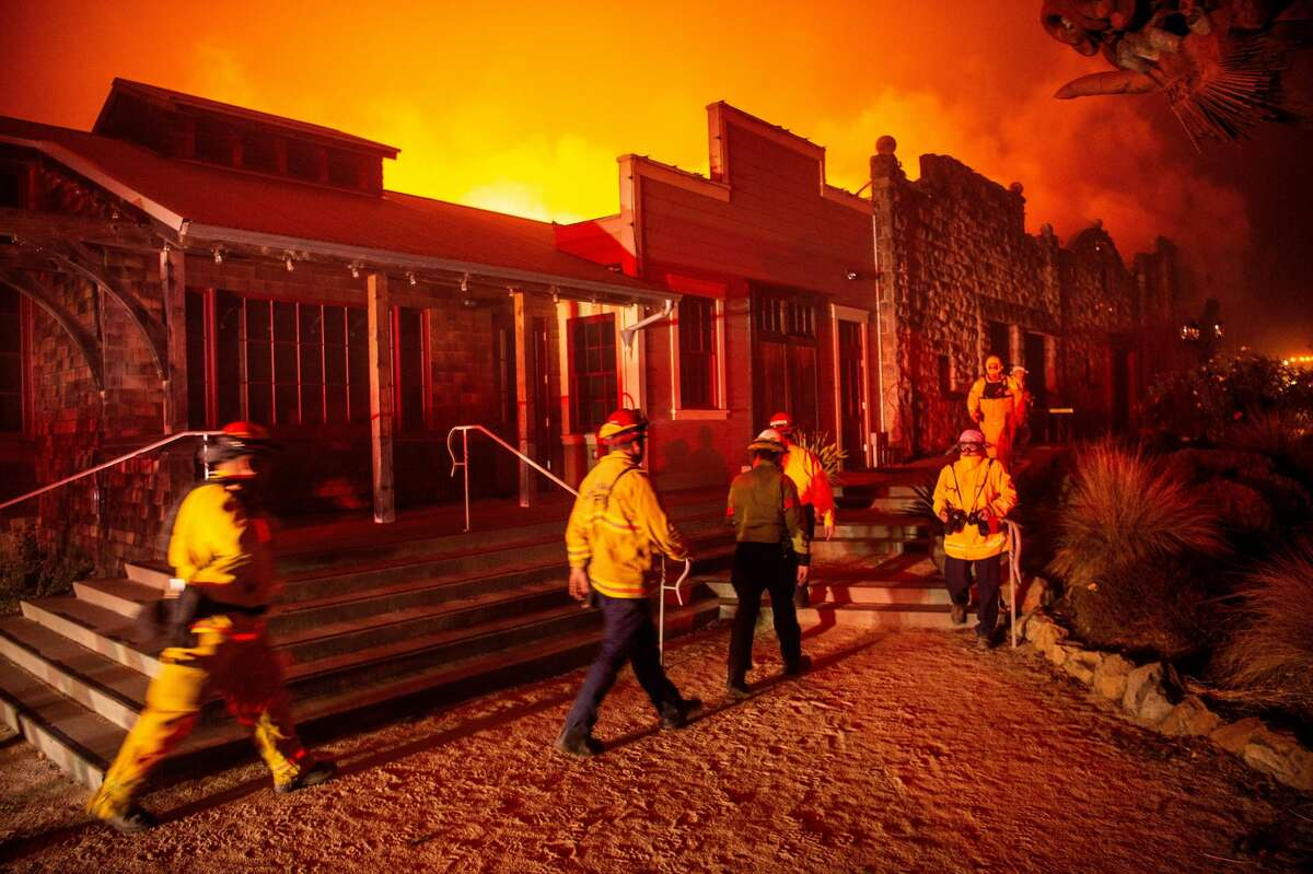 """Firefighters survey the Soda Rock Winery as it burns during the Kincade fire as flames race through Healdsburg, California on October 27, 2019. - Powerful winds were fanning wildfires in northern California in """"potentially historic fire"""" conditions, authorities said October 27, as tens of thousands of people were ordered to evacuate and sweeping power cuts began in the US state. (Photo by Josh Edelson / AFP) (Photo by JOSH EDELSON/AFP via Getty Images)"""