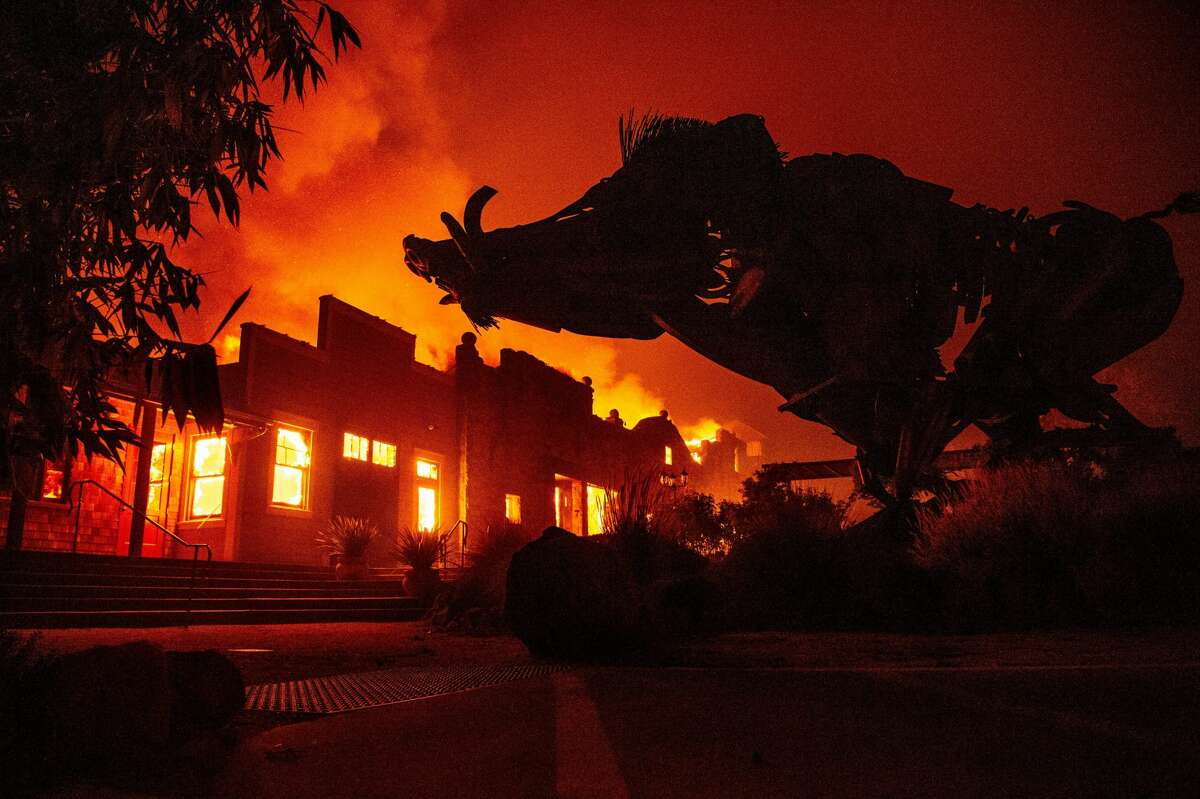"""A boar statue silhouettes against the Soda Rock Winery as it burns during the Kincade fire as flames race through Healdsburg, California on October 27, 2019. - Powerful winds were fanning wildfires in northern California in """"potentially historic fire"""" conditions, authorities said October 27, as tens of thousands of people were ordered to evacuate and sweeping power cuts began in the US state. (Photo by Josh Edelson / AFP) (Photo by JOSH EDELSON/AFP via Getty Images)"""