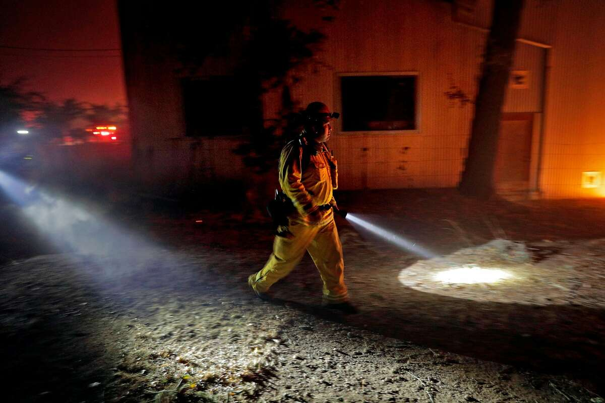 A firefighter exmaines the progress of a fire at the Soda Rock Winery as the Kincade Fire burns outside Healdsburg, Calif., on Sunday, October 27, 2019.
