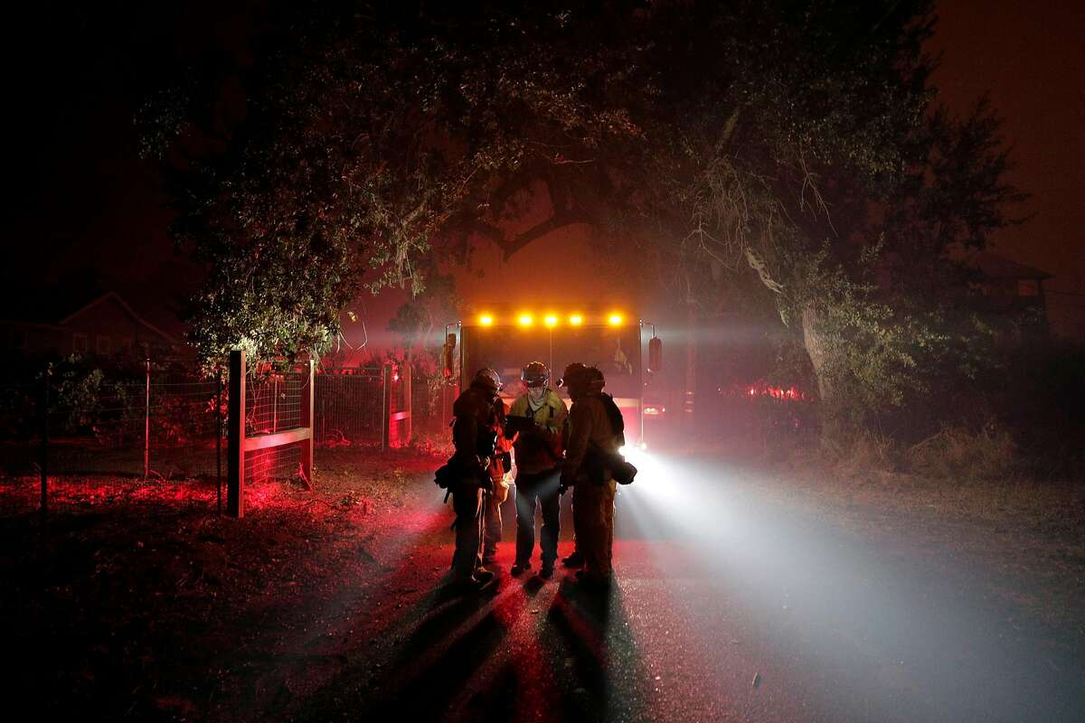 Firefighters plan their response on Soda Rock Lane as the fire crossed Highway 128 when heavy gusting winds grew the fire overnight as the Kincade Fire burns outside Healdsburg, Calif., on Sunday, October 27, 2019.
