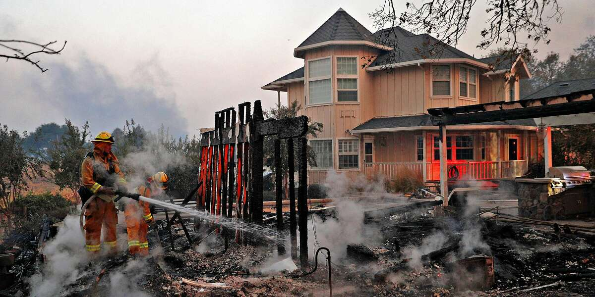 Firefighters extinguish hot spots next to a house outside Healdsburg, on October 27, 2019.