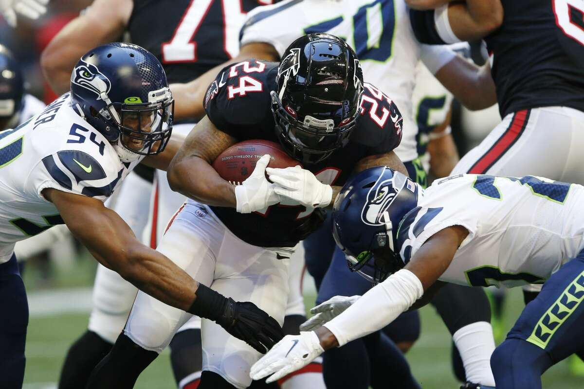 Atlanta Falcons running back Devonta Freeman (24) runs into Seattle Seahawks middle linebacker Bobby Wagner (54) during the first half of an NFL football game, Sunday, Oct. 27, 2019, in Atlanta. (AP Photo/John Bazemore)
