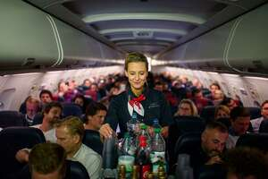An Air Berlin flight attendant serves drinks on a flight to Berlin, Germany.