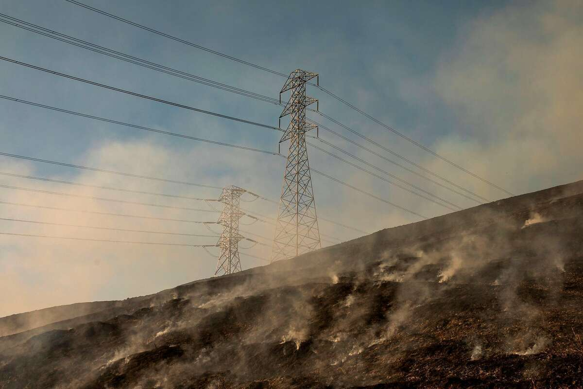 CORRECTION - Smokes rises from a back fire set by fire fighters near a hillside near PG&E power lines during firefighting operations to battle the Kincade Fire in Healdsburg, California on October 26, 2019. - US officials on October 26 ordered about 50,000 people to evacuate parts of the San Francisco Bay area in California as hot dry winds are forecast to fan raging wildfires. (Photo by Philip Pacheco / AFP) / The erroneous source appearing in the metadata of this photo by Philip Pacheco has been modified in AFP systems in the following manner: [AFP] instead of [www.philippachecophoto.com]. Please immediately remove the erroneous mention from all your online services and delete it from your servers. If you have been authorized by AFP to distribute it to third parties, please ensure that the same actions are carried out by them. Failure to promptly comply with these instructions will entail liability on your part for any continued or post notification usage. Therefore we thank you very much for all your attention and prompt action. We are sorry for the inconvenience this notification may cause and remain at your disposal for any further information you may require. (Photo by PHILIP PACHECO/AFP via Getty Images)