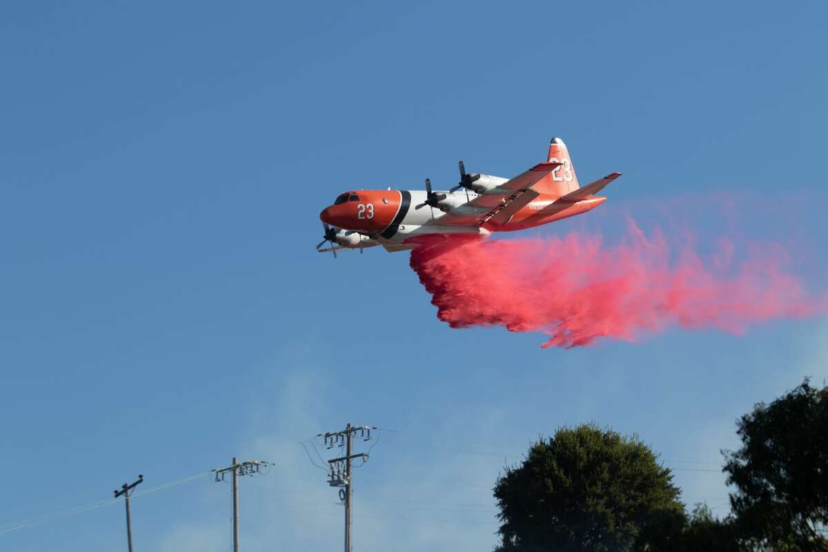 A tanker drops a load of retardant as a fire burns from the Glen Cove neighborhood, over Interstate 80 and into the CSU California Maritime Academy campus in Vallejo on Sunday, Oct. 27, 2019