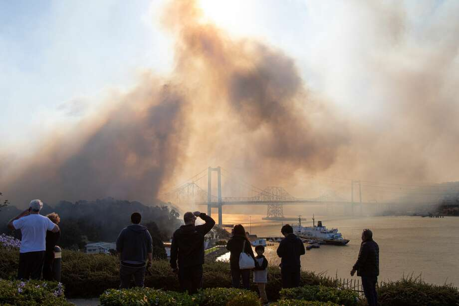 Residents watch from Jade Circle as a fire burns from the Glen Cove neighborhood, over Interstate 80 and into the CSU California Maritime Academy campus in Vallejo on Sunday, Oct. 27, 2019 Photo: Chris Preovolos