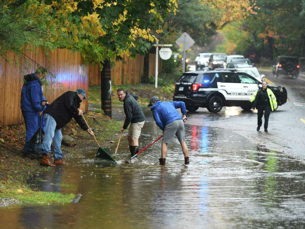 A group of neighbors work together to unclog a storm drain that has caused flooding to block Hoyt Street in Darien, Conn. Sunday, Oct. 27, 2019. The area received almost two inches of rain, causing heavy flooding and problems with traffic flow through town.