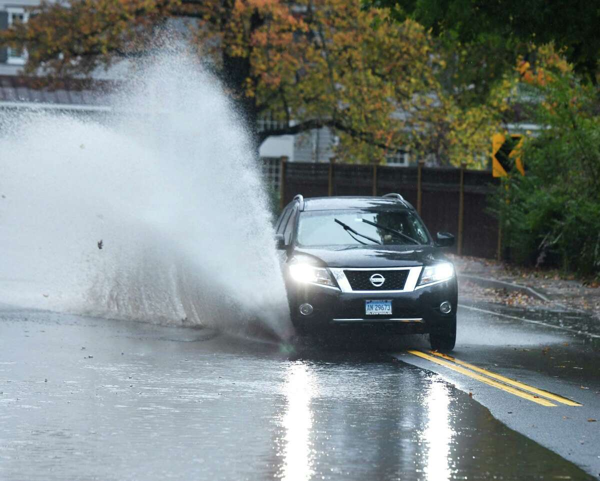 A car splashes through a flooded area along Hoyt Street in Darien, Conn. Sunday, Oct. 27, 2019. The area received almost two inches of rain, causing heavy flooding and problems with traffic flow through town.