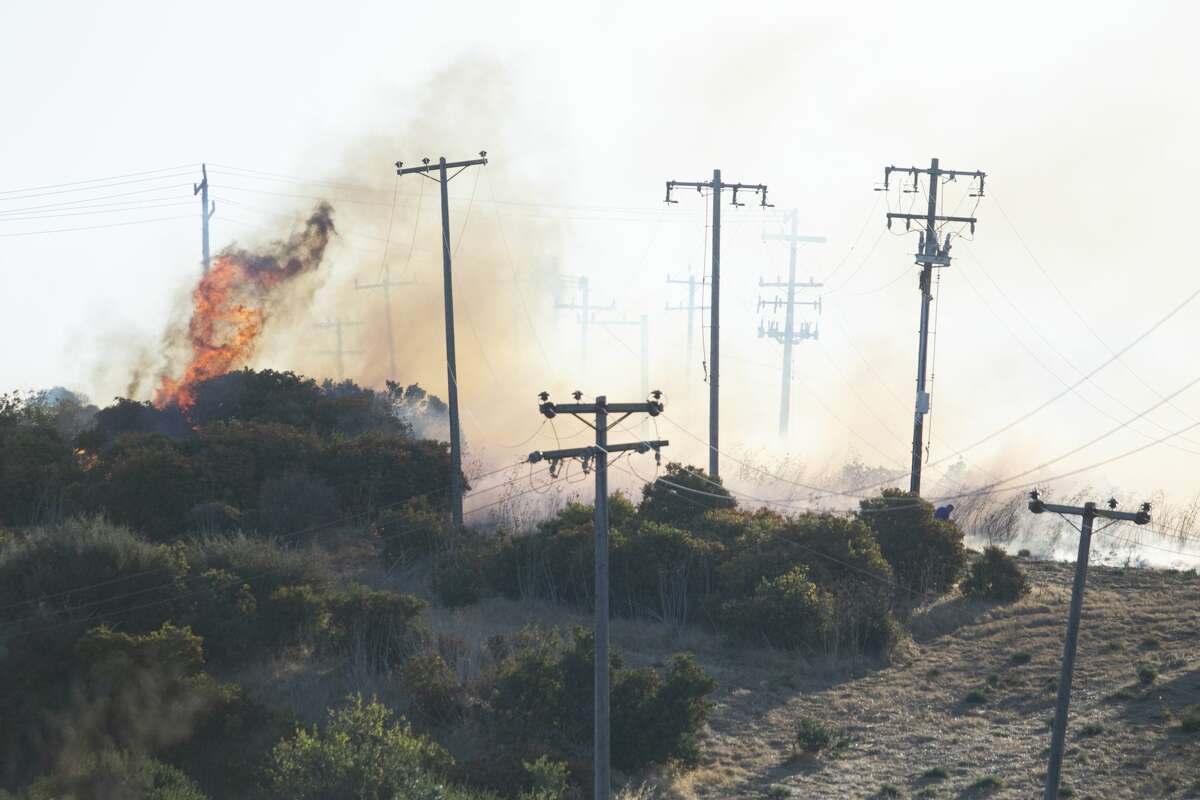 A fire burns hear power lines as it burns from the Glen Cove area, over Interstate 80 and into the CSU California Maritime Academy campus in Vallejo on Sunday, Oct. 27, 2019