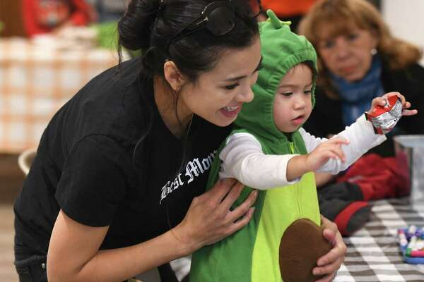 Dallas residents Bianca Wolf and Luna Wolf, 1, get candy at the Trick or Treat on the Farm event at the Stamford Museum & Nature Center in Stamford, Conn. Sunday, Oct. 27, 2019. Due to rain the event was moved indoors, but still delighted costumed kids with a variety of activities including coloring, crafts, live animals on display, a touch and texture station, oversized Jenga, and more.