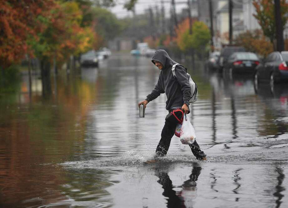 A man crosses a flooded Iranistan Avenue in Bridgeport, Conn. during heavy rains on Thursday, October 24, 2019. Photo: Brian A. Pounds / Hearst Connecticut Media / Connecticut Post