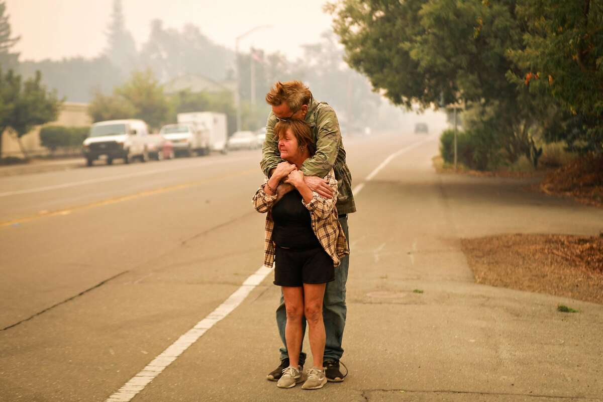 Kathy Wheeler and her husband (wished to remain anonymous) embrace as they decided not to evacuate their home despite evacuation orders during the Kincade fire in Windsor, California, on Sunday, Oct. 27, 2019.