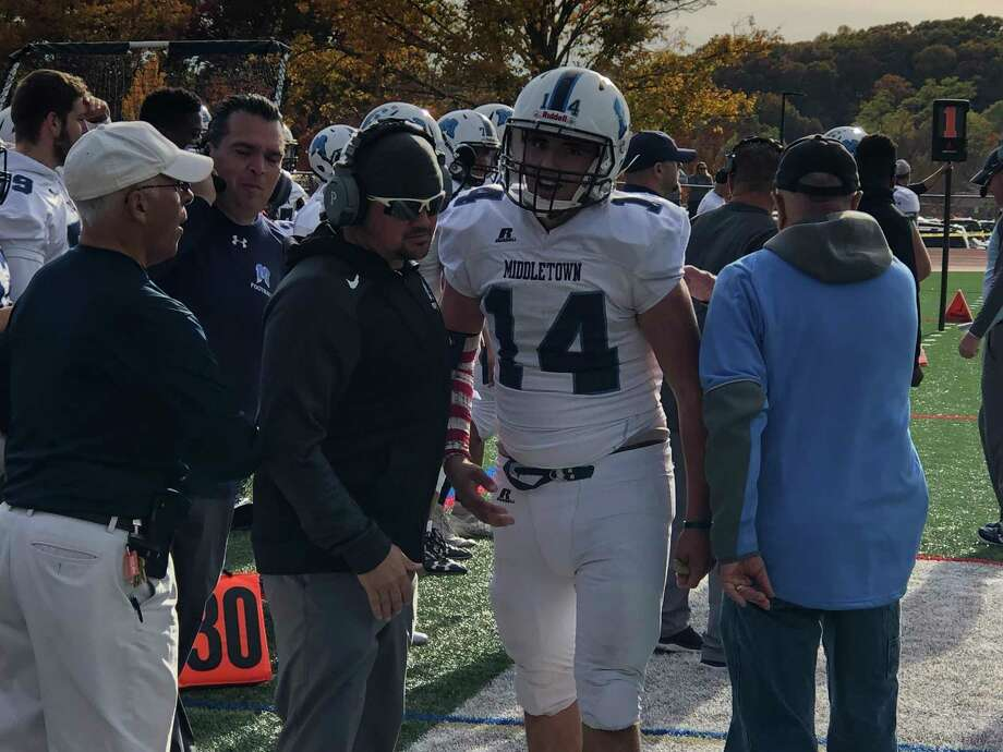 Chris Danas is met on the sideline by Middletown's coaching staff after throwing an 87-yard touchdown to Anthony Pappa in the third quarter Saturday. Photo: Paul Augeri / For Hearst Connecticut Media