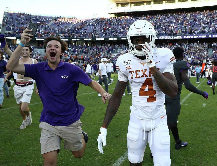 A TCU fan storms the field past UT defensive back Anthony Cook after the Horned Frogs' 37-27 upset of then-No. 15 Texas. Photo: Ronald Martinez /Getty Images / 2019 Getty Images