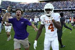 A TCU fan storms the field past UT defensive back Anthony Cook after the Horned Frogs' 37-27 upset of then-No. 15 Texas.