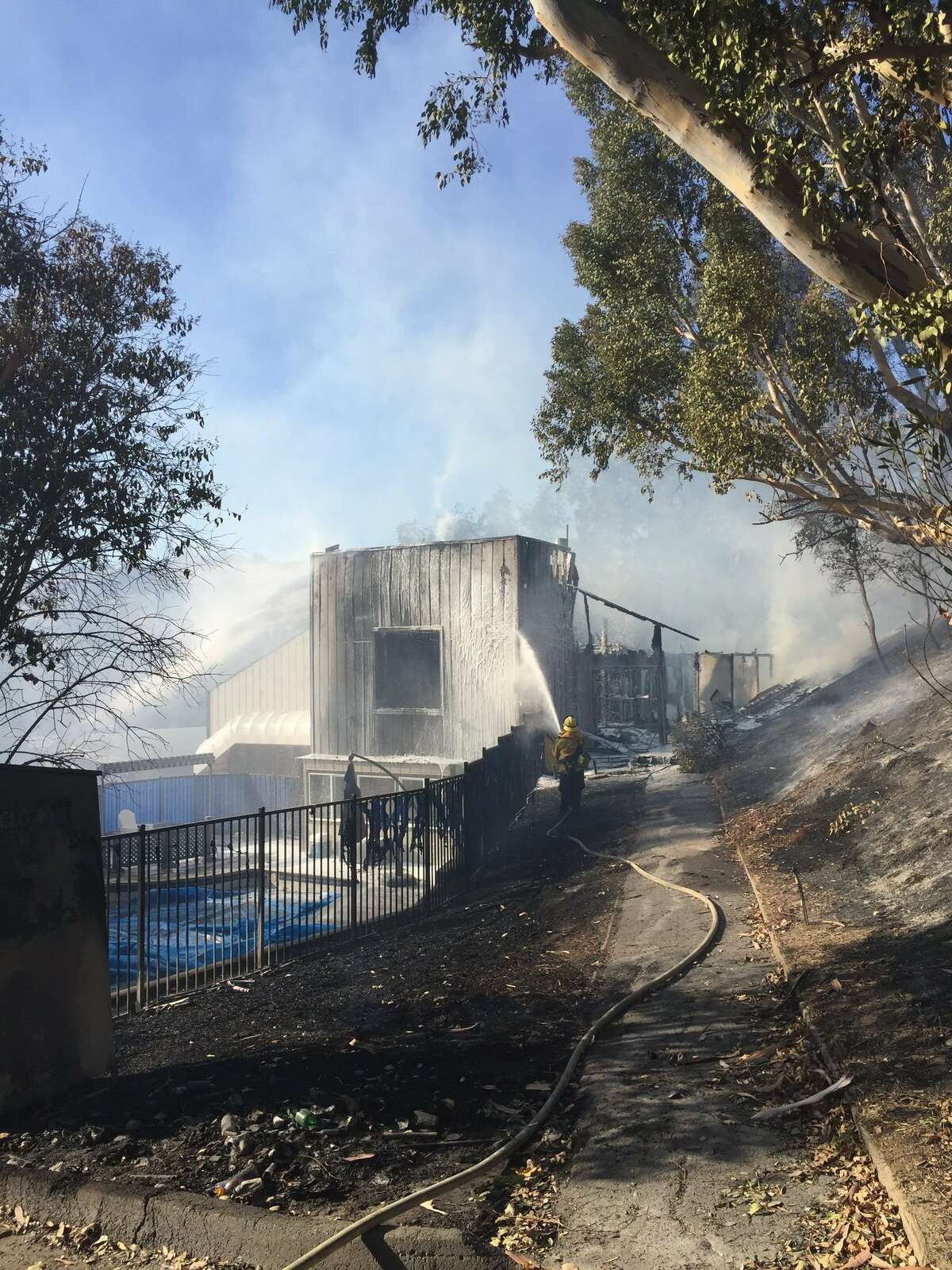 Photos show firefighters hosing down the damaged tennis club building.