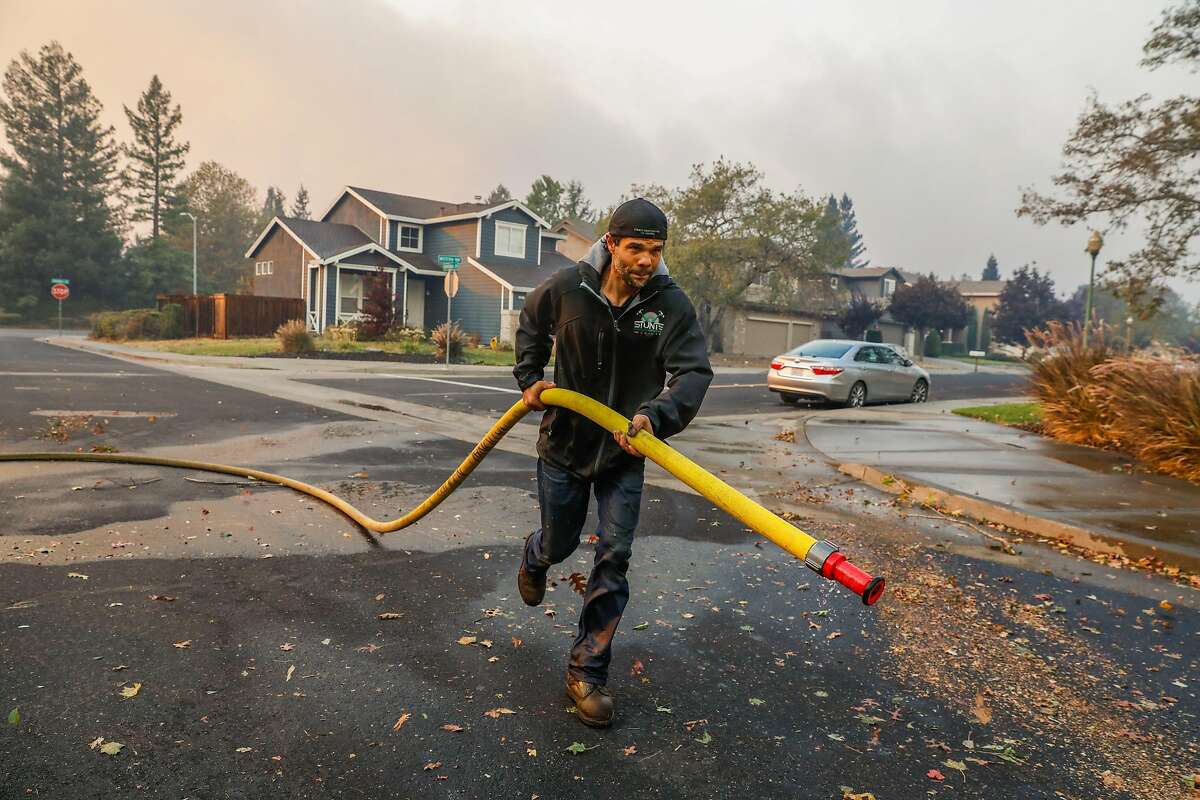 Mike Costlow tries to save his neighbors homes by spraying water on them during the Kincade fire in Windsor, California, on Sunday, Oct. 27, 2019. Mike defied the evacuation order and has been staying home to protect his house and his neighbors homes.