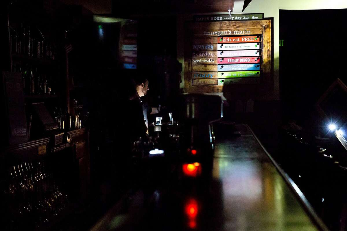 Employees use flashlights to maneuver around the bar at Finnigan's Marin Restaurant and Bar in Novato, Calif. during PG&E's Marin County power shut down on Saturday, Oct. 26, 2019. Residents throughout the North Bay are expected be without power starting Saturday evening as PG&E begins it's second Public Safety Power Shut-Off. PG&E states that over 940,000 residents will be without power through the weekend.