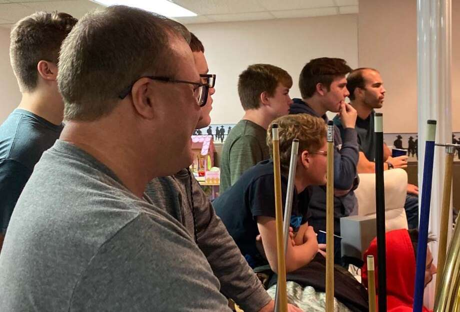 North Huron head football coach Chad Knoblock, foreground, and members of his team watch the MHSAA announcement of the 2019 playoff matchups on Sunday night in at the Knoblock home in Kinde. Photo: Mark Birdsall/Huron Daily Tribune