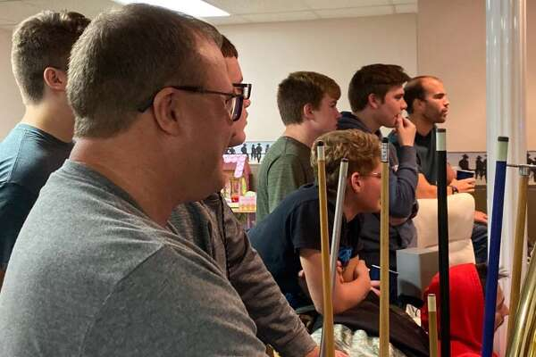 North Huron head football coach Chad Knoblock, foreground, and members of his team watch the MHSAA announcement of the 2019 playoff matchups on Sunday night in at the Knoblock home in Kinde.