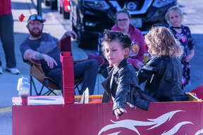 Two youngsters dressed as greasers cruise Hartford's Delmar Avenue in their custom hot rod Sunday during the village's annual Halloween parade.