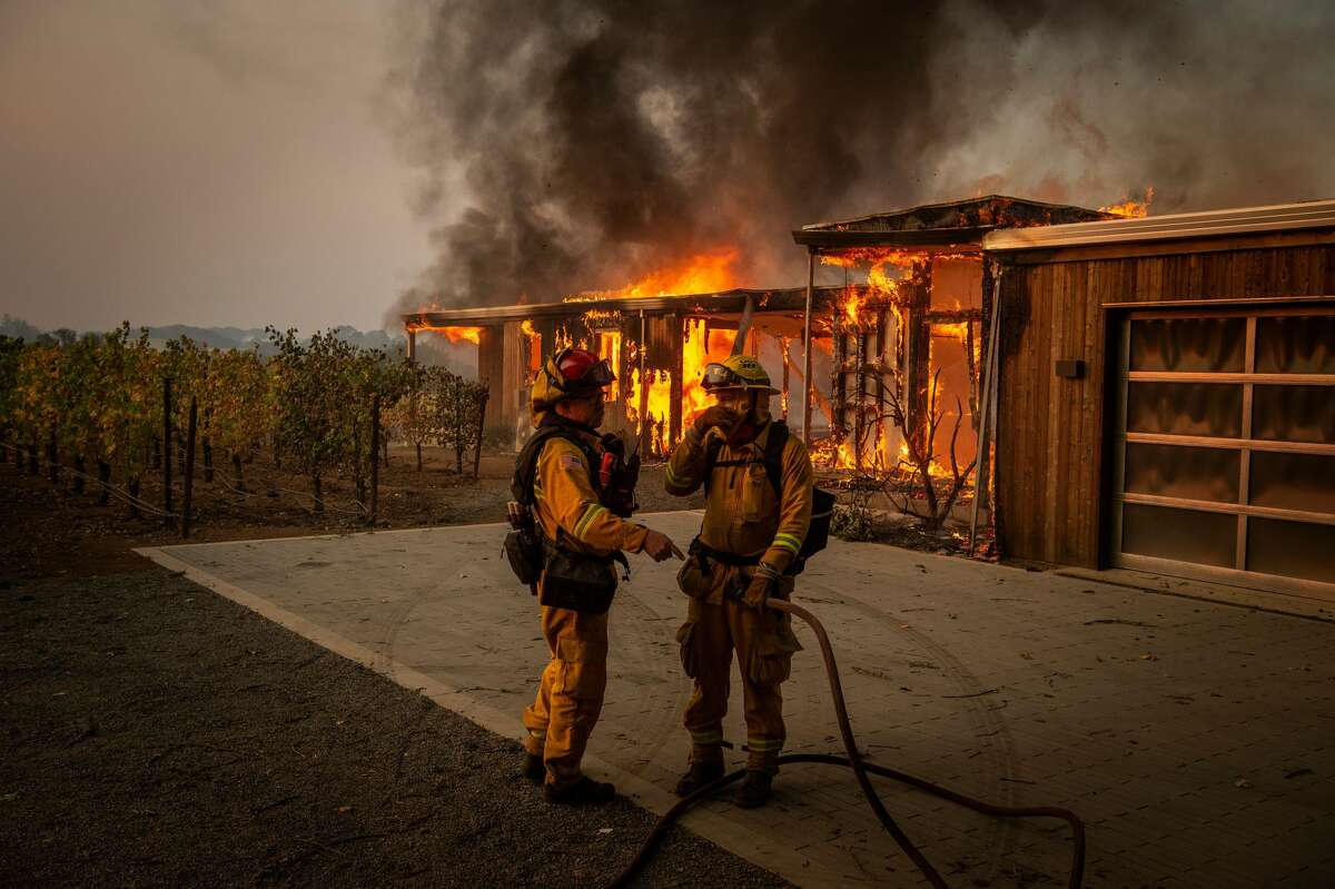Firefighters discuss how to approach the scene as a home burns near grapevines during the Kincade fire in Healdsburg on October 27, 2019. Powerful winds were fanning wildfires in Northern California.