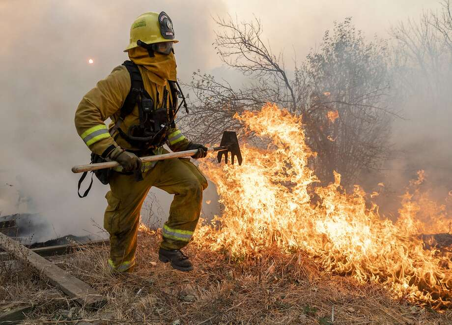 A firefighter from San Matteo helps fight the Kincade Fire in Sonoma County, Calif., on Sunday, Oct. 27, 2019. (AP Photo/Ethan Swope) Photo: Ethan Swope / Associated Press