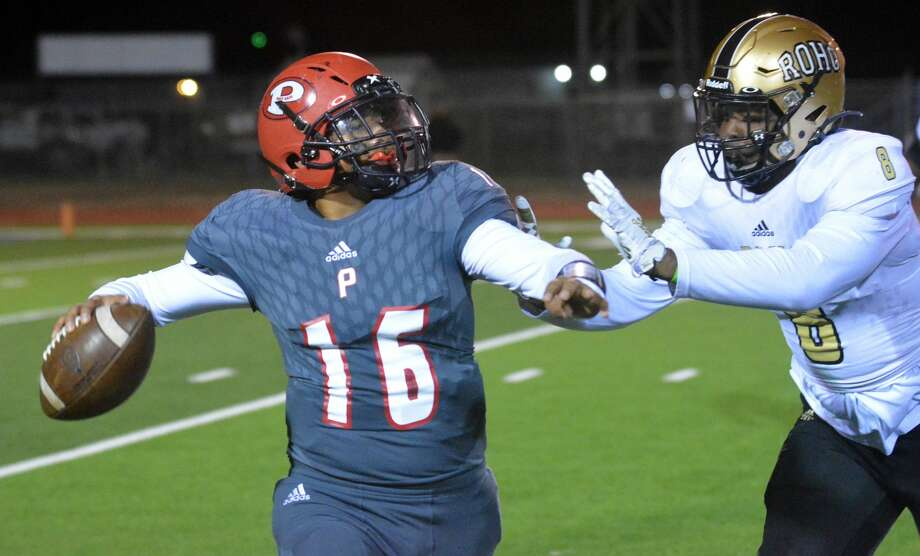 Plainview quarterback Tyler Rodriguez attempts to get the ball away before Wichita Falls Rider defender E'Maurion Banks can take him down during their District 3-5A Division II football one Friday night in Greg Sherwood Memorial Bulldog Stadium. Photo: Nathan Giese/Planview Herald
