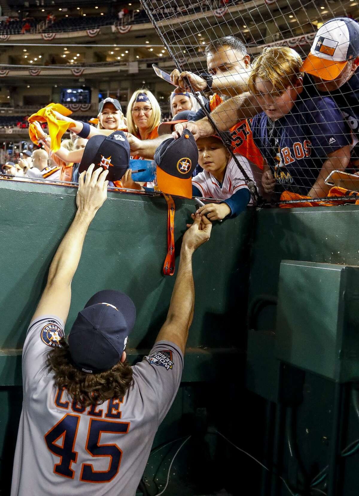 Houston Astros starting pitcher Gerrit Cole (45) signs autographs for fans after the Astros won Game 5 of the World Series 7-1 at Nationals Park in Washington, D.C. on Sunday, Oct. 27, 2019.