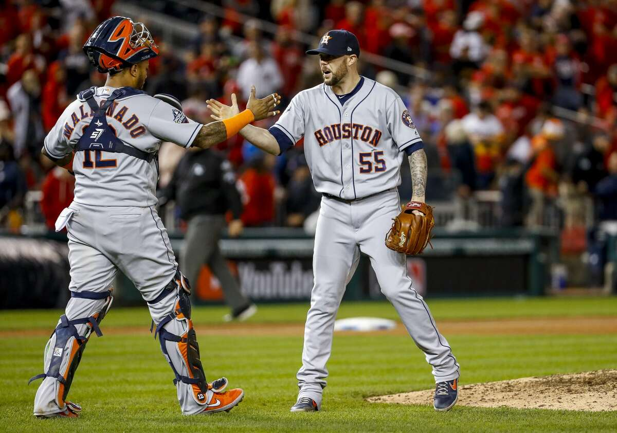 Houston Astros catcher Martin Maldonado (12) and Houston Astros relief pitcher Ryan Pressly (55) celebrate as the Astros win 7-1 in Game 5 of the World Series at Nationals Park in Washington, D.C. on Sunday, Oct. 27, 2019.