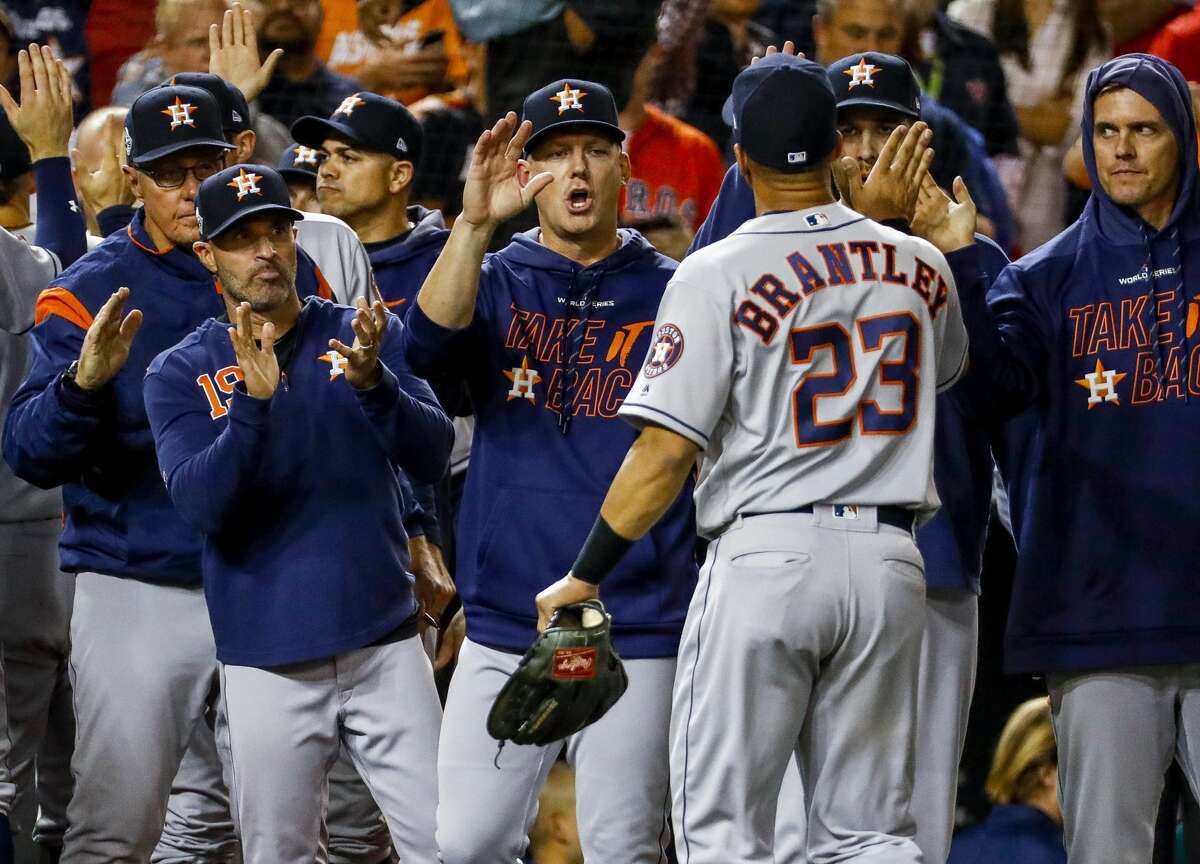 Houston Astros left fielder Michael Brantley (23) is high-fived by members of the Astros coaching staff after the team's 7-1 win of Game 5 of the World Series at Nationals Park in Washington, D.C. on Sunday, Oct. 27, 2019.