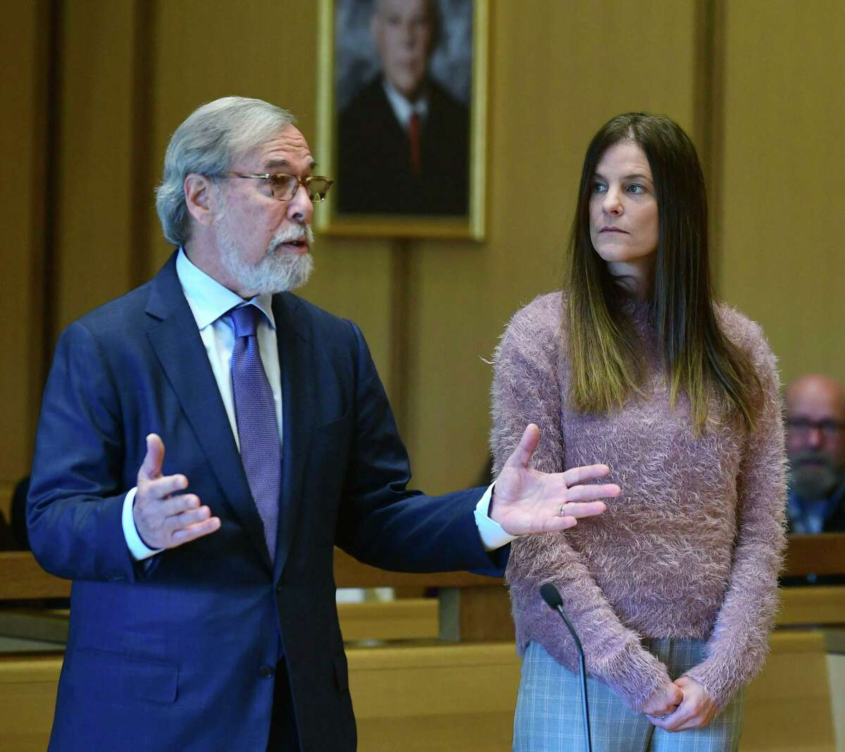 Michelle Troconis, charged with two counts of tampering with evidence and hindering prosecution in the disappearance of Jennifer Dulos, listens to her attorney Andrew Bowman while appearing for a pre-trial hearing Friday, Oct. 25, 2019, at the Stamford Superior Court in Stamford, Conn.