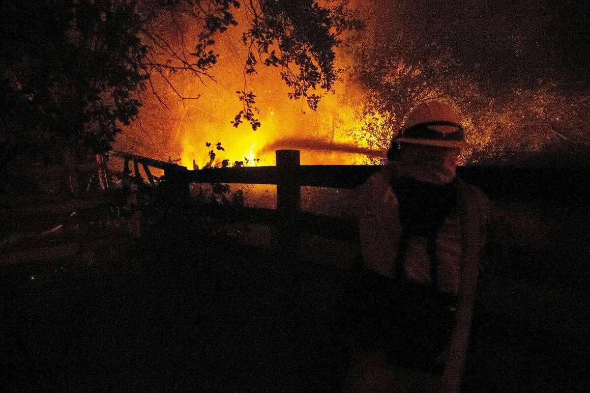 Richard Lais of the Palo Alto Fire Department battles the Kincade Fire along Chalk Hill Road on Sunday, Oct. 27, 2019, in Healdsburg, Calif.