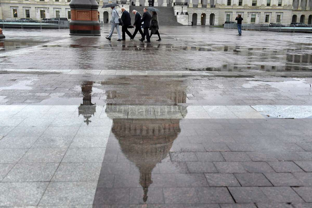 The Capitol dome is reflected in a rain puddle on Oct. 22, 2019.