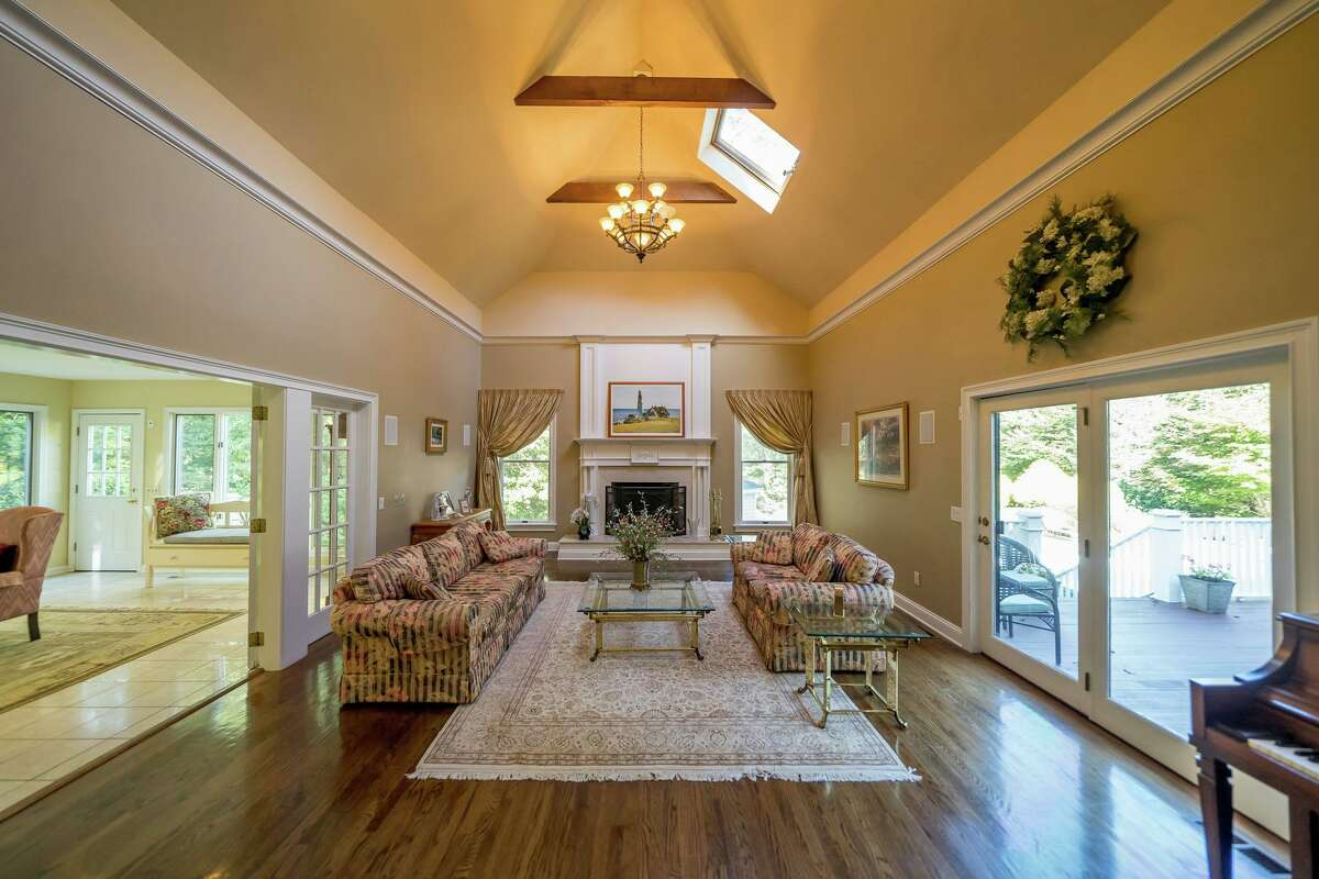The living room features a cathedral ceiling with exposed beams, skylights, a fireplace with a decorative mantel, an interior balcony, and sliding doors to the deck and yard.