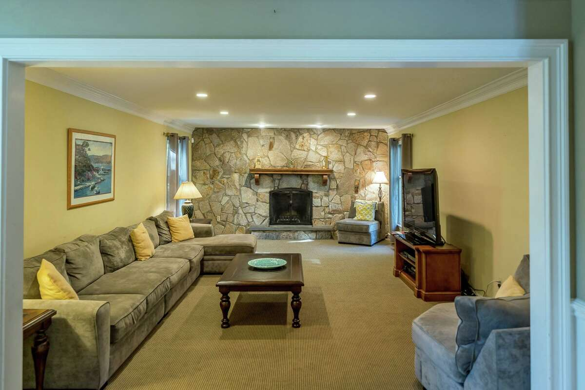 The family room has wall-to-wall carpeting and one entire stone wall that houses the fireplace with a raised hearth.