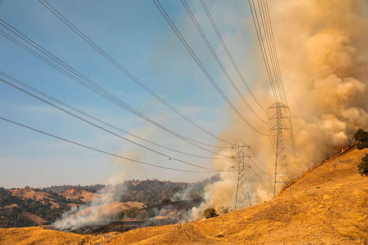 TOPSHOT - A back fire set by fire fighters burns a hillside behind PG&E power lines during firefighting operations to battle the Kincade Fire in Healdsburg, California on October 26, 2019. - US officials on October 26 ordered about 50,000 people to evacuate parts of the San Francisco Bay area in California as hot dry winds are forecast to fan raging wildfires. (Photo by Philip Pacheco / AFP) (Photo by PHILIP PACHECO/AFP via Getty Images)