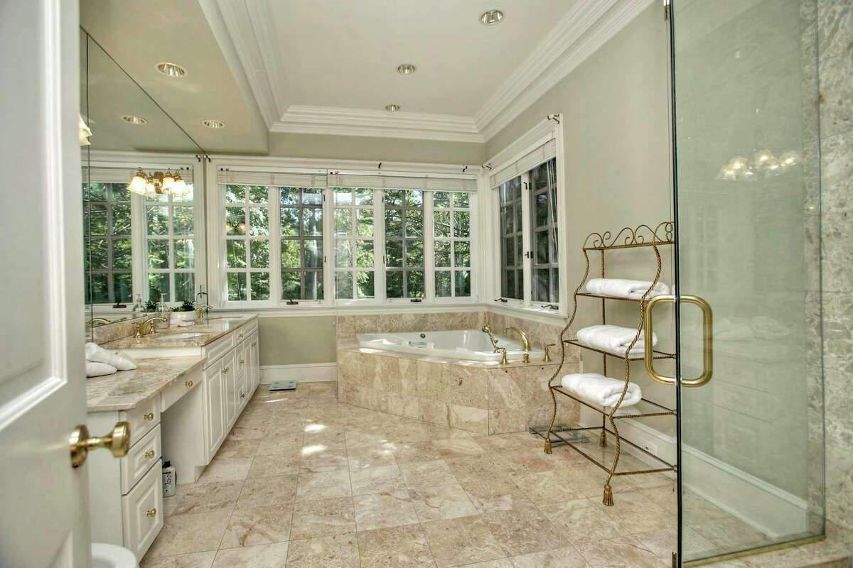 The luxurious marble master bath features a double vanity, jetted tub and shower.