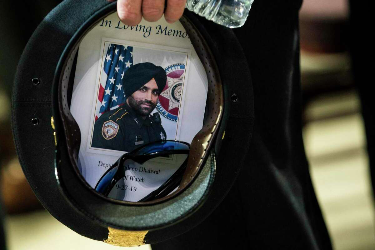 A Houston Police officer places a picture of Harris County Sheriff's Deputy Sandeep Dhaliwal in his hat during the deputy's funeral at Berry Center on Wednesday, Oct. 2, 2019, in Houston. Dhaliwal was killed in the line of duty Sept. 27, 2019, when he was shot during a traffic stop. (Brett Coomer/Houston Chronicle via AP)