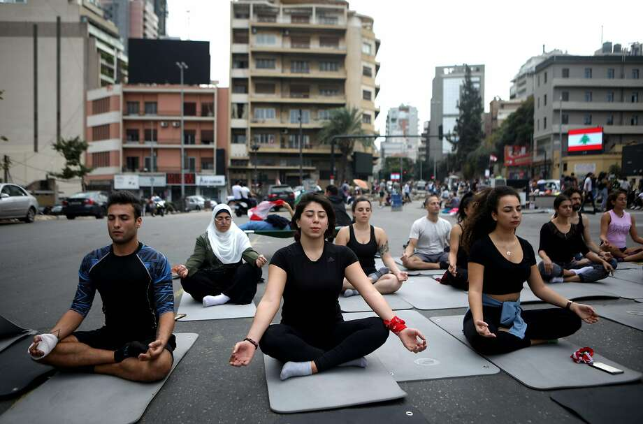 Anti-government activists practice yoga on a blocked avenue in Beirut. Protesters have grown more inventive in blocking roads as part of demonstrations under way for the last 12 days. Photo: Patrick Baz / AFP Via Getty Images
