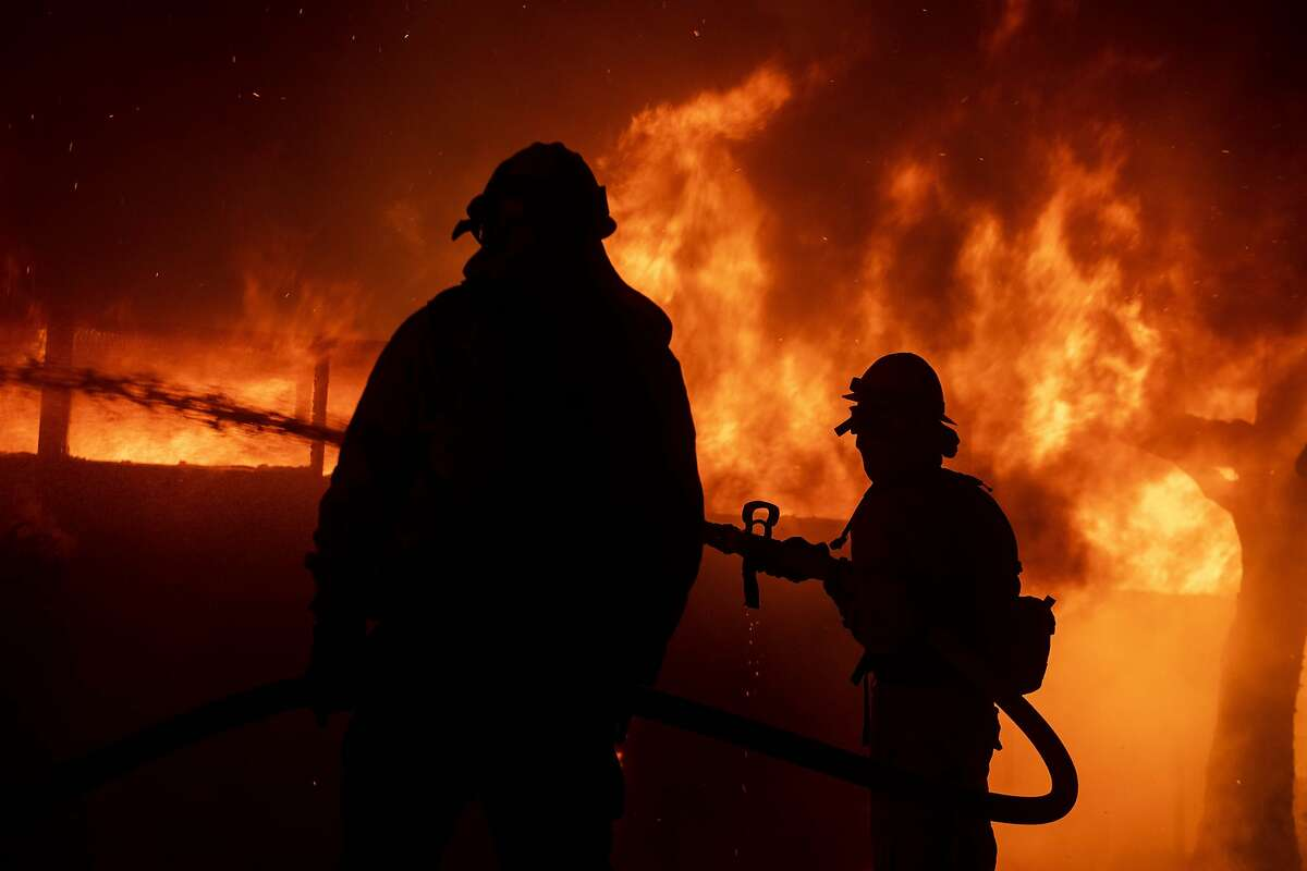 Firefighters try to save a home on Tigertail Road during the Getty fire, Monday, Oct. 28, 2019, in Los Angeles, Calif.