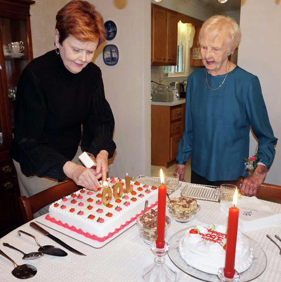 Margaret Cochran, of Godfrey, right, watches as her daughter, Elizabeth Blake, of Naperville, prepares a cake as part of a 100th birthday celebration Saturday. Originally from Ontario, Cochran for years was an organist at the First Baptist Church in Alton and the Upper Alton Baptist Church.