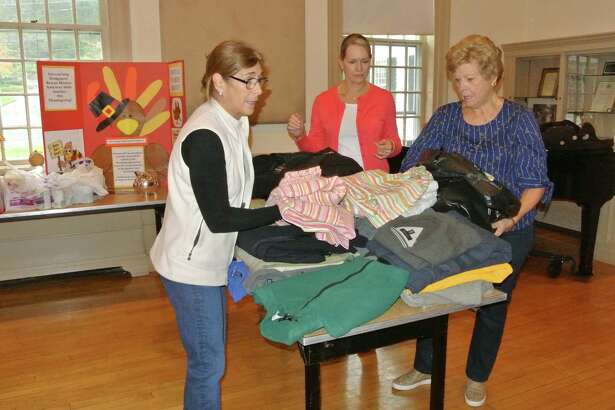 From left, Marie Broderick, Kathy Scheller, and Carol Boehly sort donated coats and linens during a previous coat drive at the Wilton Congregational Church.