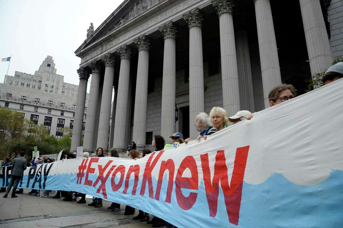 Protesters rally outside State Supreme Court in Manhattan on Tuesday, Oct. 22, 2019. After four years of legal sparring and finger-pointing, oil-industry giant Exxon Mobil went to court on Tuesday to face charges that the company lied to shareholders and to the public about the costs and consequences of climate change. (Jefferson Siegel for The New York Times)