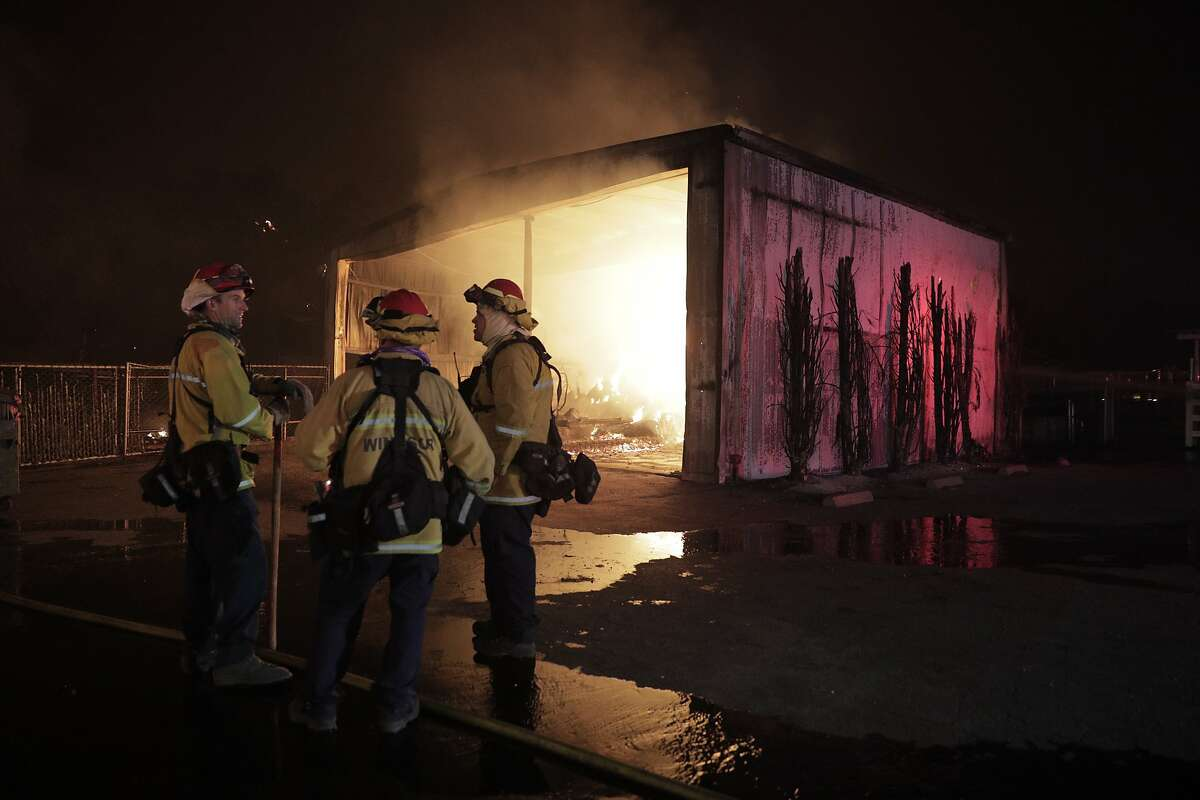 Firefighters monitor a hay barm burning while protecting other structures at Fieldstone Farms as the Kincade Fire continues to burn in Windsor, Calif., on Sunday, October 27, 2019.