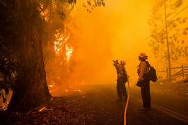 (FILES) In this file photo taken on October 27, 2019 firefighters battle the Kincade Fire along Chalk Hill Road in Healdsburg, California on October 27, 2019. - California's governor declared a statewide emergency on October 27, 2019 as a huge blaze, fanned by strong winds, forced mass evacuations and power blackouts as it bore down on towns in the famed Sonoma wine region.The so-called Kincade Fire, north of San Francisco, has spread to 30,000 acres (12,000 hectares) and was only 10 percent contained by Sunday evening, state fire authorities said. (Photo by Philip Pacheco / AFP) (Photo by PHILIP PACHECO/AFP via Getty Images)