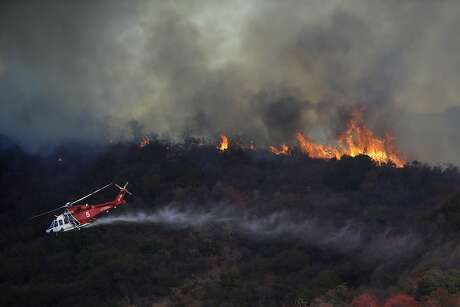 A wildfire called the Getty Fire burns a ridge top as a water-dropping helicopter flies by on Mandeville Canyon Monday, Oct. 28, 2019, in Los Angeles. (AP Photo/Marcio Jose Sanchez)